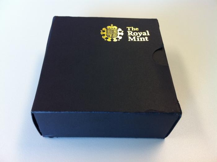 A caixa que a moeda vem é de extremo bom gosto, bem estilão britânico, com aquele tom de material oficial...