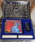 """Abrindo-se a caixa, é possível apreciar o itens devidamente alojados em um bonito revestimento aveludado. Os CDs ficam colocados em 3 níveis onde, pela cor, é possível entender qual é qual. Ao lado, o copinho (que serve também como porta-velas) e a """"árvore genealógica"""" da banda com um anel do Eddie também em metal"""